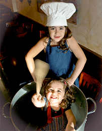 Phil Nicosia's two daughters, one sitting in a pot, the other wearing a chef hat and standing next to the pot