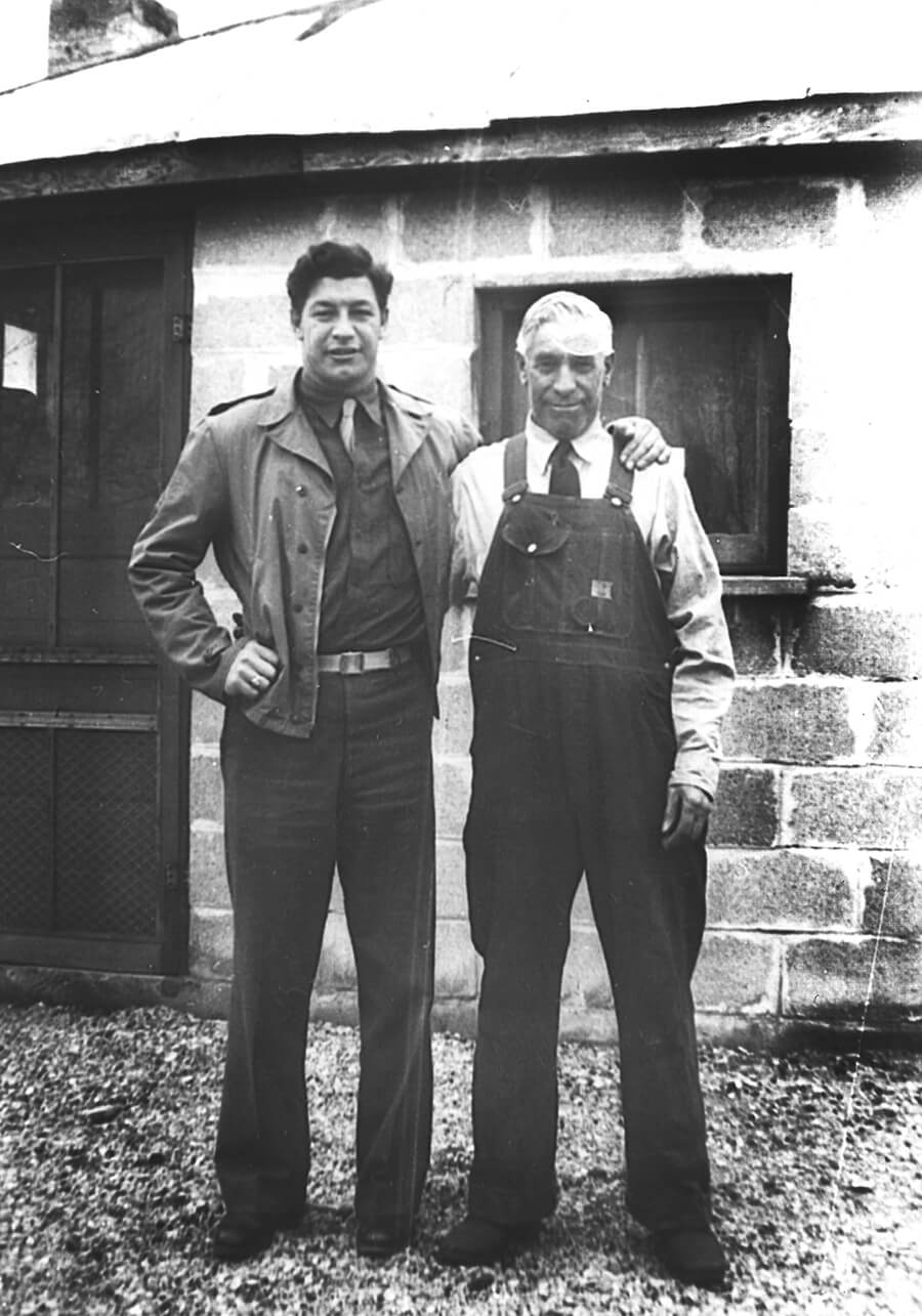 black and white photo of two men standing in front of a house