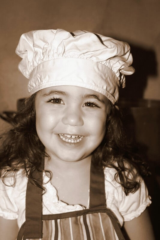 Phil Nicosia's daughter smiling in her apron and chefs hat