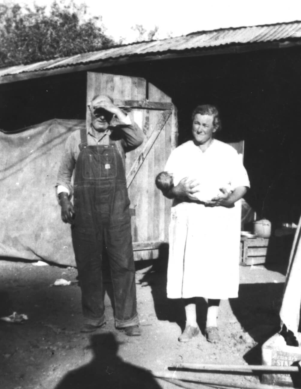 black and white photo of a man covering his eyes from the sun while a woman in a white dress holds a baby